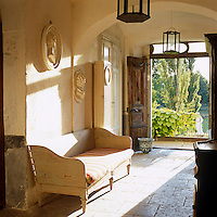 Sunlight floods in through the open front doors into the entrance hall