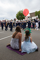 Mother and daughter sitting, watching the Independence Day Parade 2016, Burien, Washington, USA.