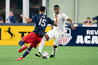 FOXBOROUGH, MA - MAY 22: Andres Reyes #4 of New York Red Bulls dribbles past Brandon Bye #15 of New England Revolution during a game between New York Red Bulls and New England Revolution at Gillette Stadium on May 22, 2021 in Foxborough, Massachusetts.