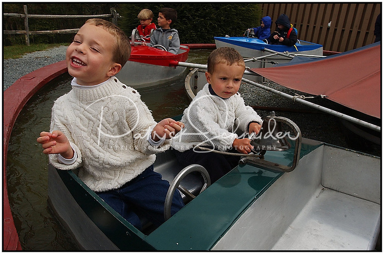 Two boys ride on a boat ride at the Tweetsie Railroad amusement park in the Blue Ridge Mountains between Blowing Rock and Boone, North Carolina. Boys are model released.