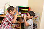 Education preschool 3-4 year olds two boys laughing and looking at each other through binoculors made from tape and cardboard tubes horizontal