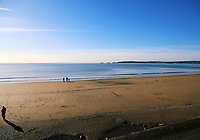 A young family enjoy a day of sunshine on the sandy beach in Swansea Bay, Wales, UK. Friday 27 October 2017