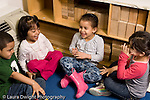 Education preschool 4 year olds group of 3 girls and a boy sitting together talking and laughing horizontal