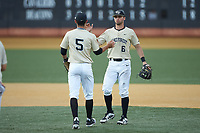 Wake Forest Demon Deacons second baseman Jake Mueller (6) celebrates with shortstop Patrick Frick (5) following their win over the Virginia Cavaliers at David F. Couch Ballpark on May 19, 2018 in  Winston-Salem, North Carolina. The Demon Deacons defeated the Cavaliers 18-12. (Brian Westerholt/Four Seam Images)