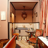 In an Empire-style Paris apartment the en-suite bathroom is situated in a tiled alcove to the side of the bedroom and is lit by its own chandelier