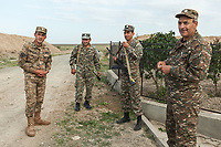 """Nagorno-Karabakh, also known as Artsakh, is a landlocked region in the South Caucasus. Merzili. Soldiers with Kalashnikov and an officer, all wearing camouflage uniforms, are distant 450 meters from the front line of the ongoing fighting with Azerbaijan. The military men stand close to the memorial of Monte Melkonian (1957 - 1993) who was an Armenian revolutionary, left-wing nationalist militant and commander. He was the leader of an offshoot of the Armenian Secret Army for the Liberation of Armenia (ASALA) in the 1980s and the most celebrated commander during the Nagorno-Karabakh War (1988-1994). Monte Melkonian was killed in 1993 by Azerbaijani soldiers while surveying Merzili with five of his comrades in the aftermath of battle. A memorial has been built where he was killed. He was declared a National Hero of Armenia in 1996. Nagorno-Karabakh is a disputed territory, internationally recognized as part of Azerbaijan, but most of the region is governed by the Republic of Artsakh (formerly named Nagorno-Karabakh Republic), a de facto independent state with Armenian ethnic population. The territory is under the control of the Artsakh Defense Army (which is backed up by Armenian Army) due to the ongoing territorial disputes with Azerbaijan. Merzili (also Mirasali) was a village and municipality in the Agdam Rayon of Azerbaijan. A Kalashnikov rifle is any one of a series of automatic rifles based on the original design of Mikhail Kalashnikov. They are officially known in Russian as """"Avtomat Kalashnikova"""" , but are widely known as Kalashnikovs, AK47s, or as a """"Kalash"""".  5.10.2019 © 2019 Didier Ruef"""