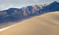 Great Sand Dunes National Park, Colorado.  Blowing sand streams off a dune with the rugged Sangre de Cristo range in the background.<br /> <br /> Canon EOS 5D Mk II, 70-200 f/2.8L lens