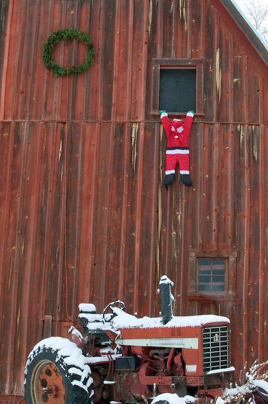 Santa Claus hanging on to window of barn. Near Lostine, Oregon
