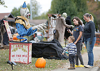 Julie Farr (from right) watches Thursday, October 15, 2020, as Bella Harrison-Rackley, 10, and her brother Noah Bohannan, 2, reacts to Halloween decorations at a home on Backus Avenue in Springdale. Farr said that visiting the decorated house is a favorite activity of Noah's and he likes to talk to the different characters. Check out nwaonline.com/201016Daily/ and nwadg.com/photos for a photo gallery.(NWA Democrat-Gazette/David Gottschalk)