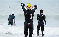17 SEP 2011 - LA BAULE, FRA - A competitor checks that his wetsuit is zipped up before having a warmup swim ahead of the final round of the men's French Grand Prix Series at the Triathlon Audencia in La Baule, France (PHOTO (C) NIGEL FARROW)