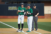 Wake Forest Demon Deacons volunteer assistant Joey Hammond (29) gives instructions to Michael Ludowig (22) as first base umpire Wilson Raynor looks on during the game against the Louisville Cardinals at David F. Couch Ballpark on March 17, 2018 in  Winston-Salem, North Carolina.  The Cardinals defeated the Demon Deacons 11-6.  (Brian Westerholt/Four Seam Images)