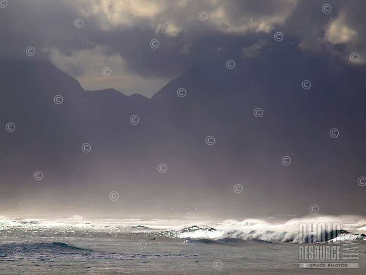 Sea spray from the crashing waves of Ho'okipa Beach, with clouds touching mountain tops in the distance, Maui.