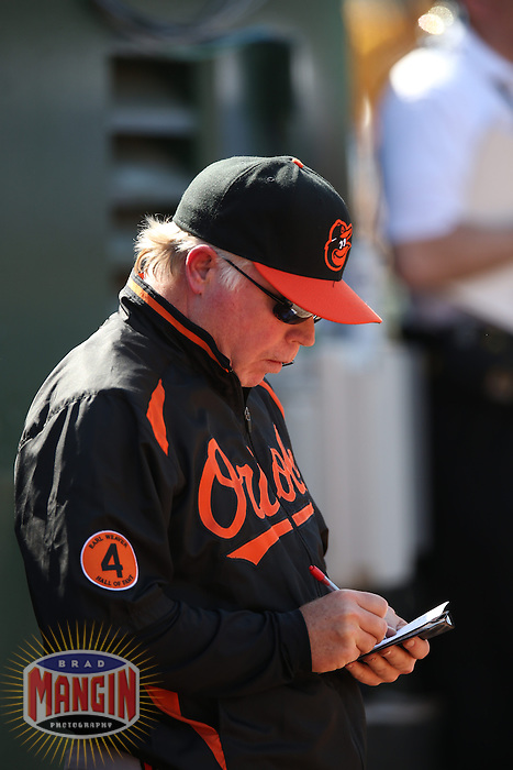 OAKLAND, CA - APRIL 28:  Manager Buck Showalter #26 of the Baltimore Orioles writes on his scorecard in the dugout during the game against the Oakland Athletics on Sunday, April 28, 2013 at The O.co Coliseum in Oakland, California. Photo by Brad Mangin