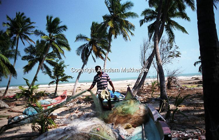 A fisherman detangles a fishing net in the Velankanni beach, Nagapattinam.India.