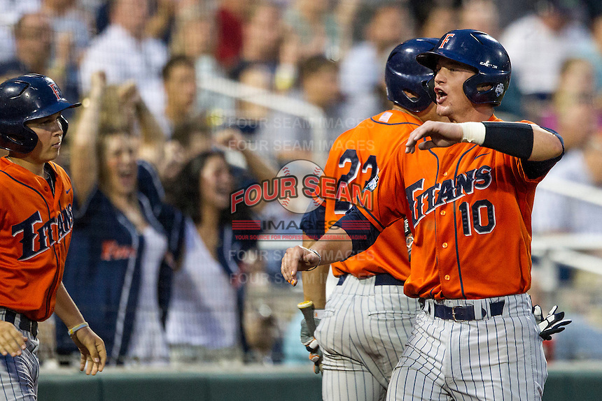 Cal State Fullerton Titans catcher A.J. Kennedy (10) is greeted after scoring during the NCAA College baseball World Series against the Vanderbilt Commodores on June 14, 2015 at TD Ameritrade Park in Omaha, Nebraska. The Titans were leading 3-0 in the bottom of the sixth inning when the game was suspended by rain. (Andrew Woolley/Four Seam Images)
