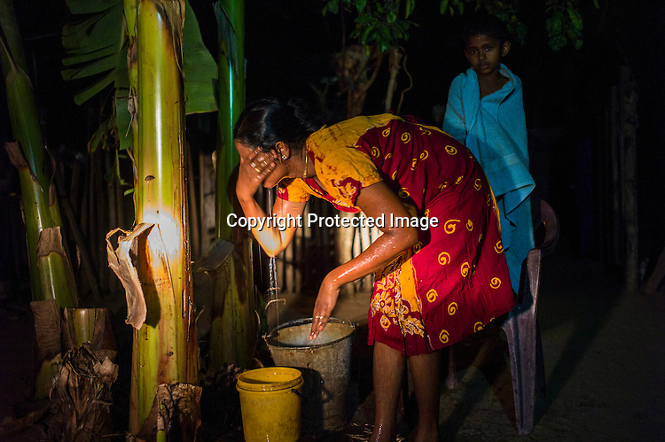 Mathumita freshens up after bathing her son at her mother's house in Punaineeravi village in Kilinochchi in Northern Sri Lanka. Photo: Sanjit Das/Panos