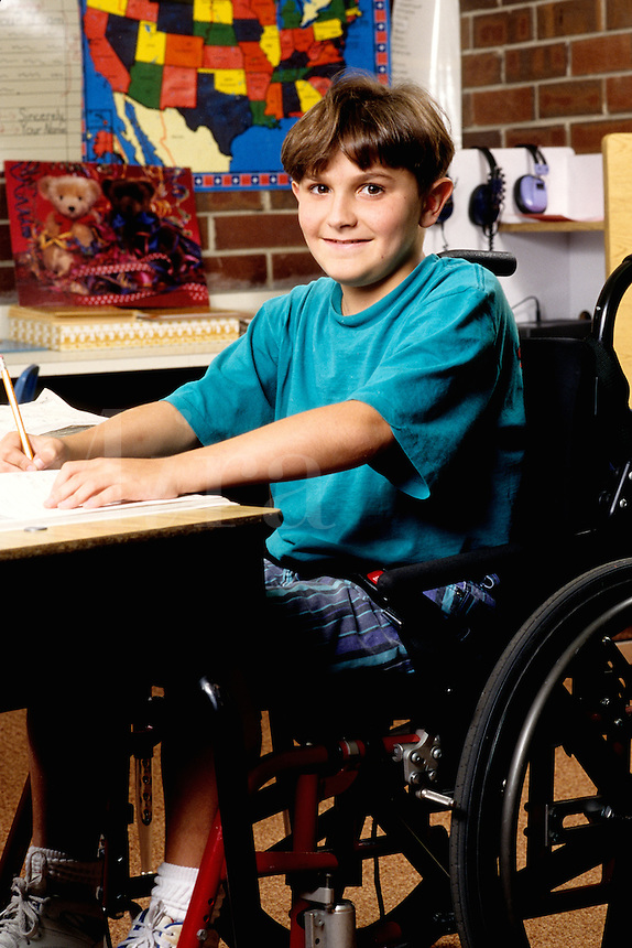 Handicapped student with energetic smile age 10 in grade 5 at desk studying and not letting handicap bother his progres
