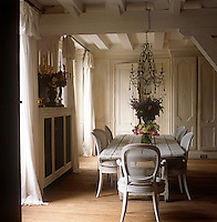 A country dining room with a painted beamed ceiling and a wood floor. A glass chandelier hangs above a rough wood table and a set of cane backed French dining chairs.