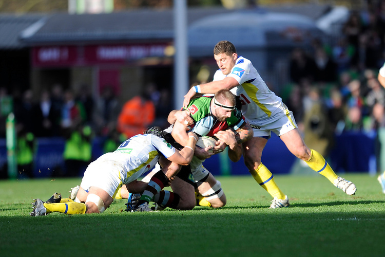 Joe Marler of Harlequins is tackled by Julien Bardy and Benjamin Kayser of ASM Clermont Auvergne during the Heineken Cup Round 5 match between Harlequins and ASM Clermont Auvergne at the Twickenham Stoop on Saturday 11th January 2014 (Photo by Rob Munro)