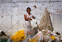 Female 'los basureros' or garbage collector, collecting plastic bags at a dumping ground in Guatemala, Latin America.