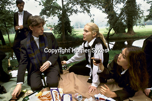 Oxford, Oxfordshire. 1995<br /> Dull but not gloomy, St Edmund Hall college freshers in subfusc picnic on the banks of the River Cherwell, drink a glass of wine or two and celebrate their success.