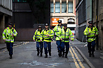 """© Joel Goodman - 07973 332324 . 22/08/2015 . Manchester , UK . Police run through along a back street to break up a fight between anti-fascists and far-right protesters . Far-right nationalist group , """" North West Infidels """" and Islamophobic , anti-Semitic and white supremacist supporters , hold a rally in Manchester City Centre . Photo credit : Joel Goodman"""