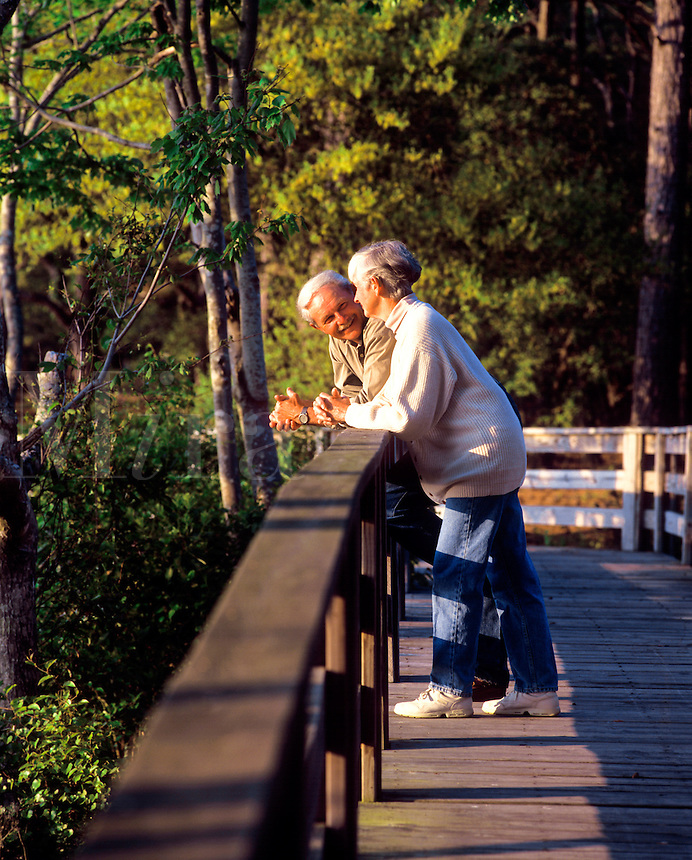 Retired couple relaxing on a foot bridge