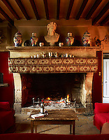 Chinese vases and a 19th century bust of Bacchus line the mantel in the dining area in which an antique farm table was cut down to serve as a cocktail table