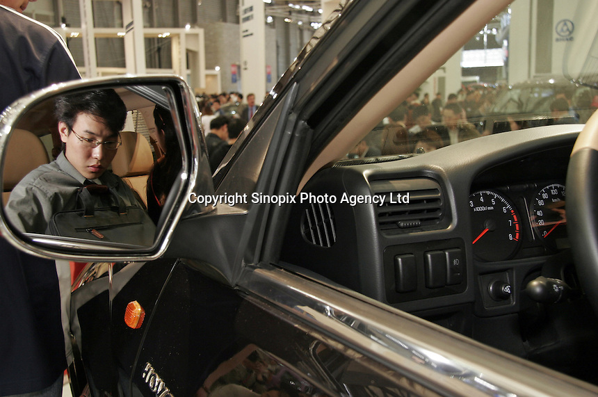 A visitor takes a seat in behind the wheel of a car at the Auto Shanghai 2005 in Shanghai, China. With global auto makers increasingly interested in the potential of the Chinese auto market, the exhibition has become one of the largest of its kind in Asia..