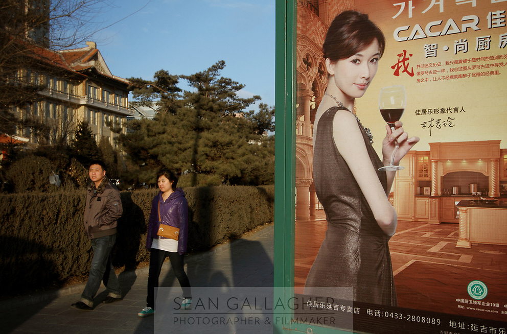 China. Jilin Province. Pedestrians walk past an advertisement in the town of Yanji, close to the border with North Korea. The town is part of the Korean Autonomous Prefecture in the north-east of the country. 2011