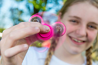 A young girl holds a pink fidget spinner