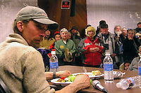 A hall full of fans watch Lance Mackey eat a steak dinner and answer questions about the trail immediately after he won the 2007 Iditarod. Photo by Jon Little.