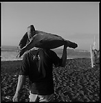 In the village of Ketewel in Bali a villager, Made, carries away a sea turtle that he bought from a traveling fisherman. The villagers made a holding area for the turtles on the beach.