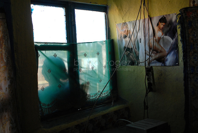 """ROMANIA, Tulcea, Viitorului Street, 2010/08/24.Half of the Roma families living in the district of Tulcea Viitorului, bordering the former industrial conglomerate, lives in France. This area is one of the poorest in the city without running water and sometimes no electricity. The street of """"future"""" is always paved. The families live mainly social benefits and hope all from one day to join Roma in Saint-Denis France). Here, a view inside a house..© Bruno Cogez..Roumanie, Tulcea, quartier de Viitorului, 24/08/2010.La moitié des familles roms vivant dans le quartier Viitorului de Tulcea, en bordure de 'lancien combinat industriel, vit en France. Ce quartier est un des plus pauvre de la ville, sans eau courante et parfois sans électricité. Les familles vivent principalement des allocations sociales et espèrent toutes partir un jour rejoindre les Roms de Saint-Denis. Ici, vue d'un intérieur d'une maison..© Bruno Cogez"""