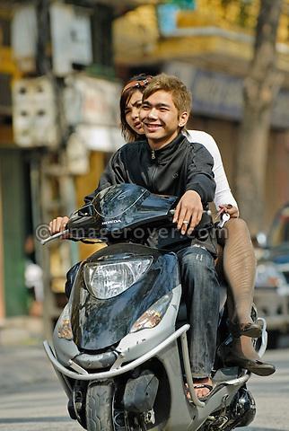 Asia, Vietnam, Hanoi. Hanoi old quarter. Cool vietnamese couple riding on a motorbike through Hanoi.