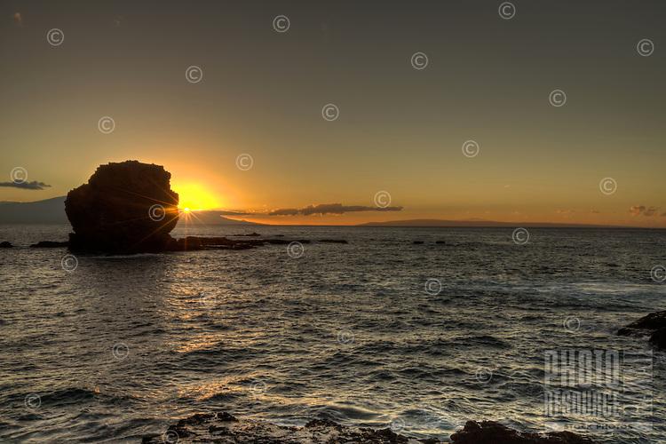 The sun sets behind Sweetheart (Pu'u Pehe) Rock near Hulopo'e Bay, Lana'i.
