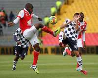 BOGOTA - COLOMBIA -22 -03-2014: Dairon Mosquera (Izq) jugador de Independiente Santa Fe disputa el balón con Javier Sanguinetti (Der) jugador de Boyaca Chico FC, durante partido por la fecha 12 de la Liga Postobon I-2014, jugado en el estadio Nemesio Camacho El Campin de la ciudad de Bogota. /  Dairon Mosquera (L) jugador of Independiente Santa Fe vies for the ball with Javier Sanguinetti (R) player of Boyaca Chico FC during a match for the 12th date of the Liga Postobon I-2014 at the Nemesio Camacho El Campin Stadium in Bogota city, Photo: VizzorImage  / Felipe Caicedo / Staff.