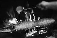 Europe/France/Midi-Pyrénées/65/Hautes-Pyrénées/Vallée du Louron/Arreau: Corinne cuit le gâteau à la broche au feu de bois dans la cheminée de sa boutique: Gourmandise Montagnarde