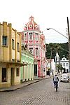 A man biking down a cobblestone street in the colonial fishing town of Laguna in Santa Catarina, Brazil