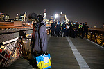 NEW YORK, NY — SEPTEMBER 25, 2020:  A homeless man walks away from a line of NYPD officers as they close the walkway on the Brooklyn Bridge during a protest against a Kentucky Grand Jury decision to not directly indict the officers involved in the shooting of Breonna Taylor, a 26 year-old EMT who was killed in her Louisville home by police on March 13th of this year, on September 25, 2020 in New York City.  Former police detective Brett Hankison faces three felony charges of wanton endangerment.  Photograph by Michael Nagle