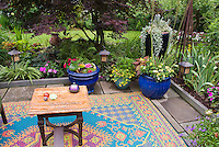 Creating an outdoor room with rugs and pot containers planters, obelisk antique ornament, table, lighting, Japanese maple tree shade garden, lawn grass, backyard living