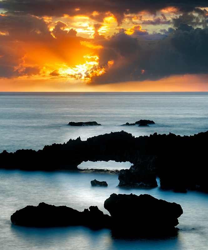 Arch and sunrise at Black Sand Beach overlook. Waianapanapa State Park, Maui, Hawaii.
