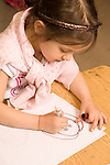 Education elementary Kindergarten art activity drawing with markers closeup of girl drawing vertical drawing human face