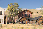 A group of old buildings at the Bannack State Park Ghost Town near Dillon Mt stands in the foreground with rolling hills and blue sky in the background. Pictured is the Hotel Meade, backside of the Masonic Lodge/School House on left and miscellaneous old buildings to the right.