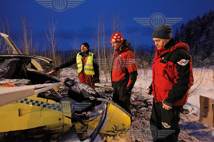 NLA staff inspect the wreckage. Norwegian Air Ambulance helicopter crash after striking power lines. It was about to land at the site of a traffic accident. The pilot and doctor were killed, while the rescue paramedic was severely injured. <br />