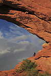 Woman visiting at Double Arch in Arches National Park, Moab, Utah, USA. .  John offers private photo tours in Arches National Park and throughout Utah and Colorado. Year-round.