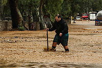 Pictured: A man walks through the flood.<br /> Re: Five people have reportedly died and severe damage caused by heavy rain and flash flooding in the area of Mandra, near Athens, Greece. Wednesday 15 November 2017