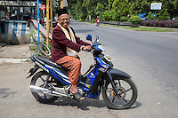 Borobudur, Java, Indonesia.  Imam from Neighborhood Mosque Going Home after Friday Noon Prayers.