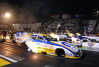 Feb 7, 2014; Pomona, CA, USA; NHRA funny car driver Matt Hagan (near lane) races alongside Tommy Johnson Jr during qualifying for the Winternationals at Auto Club Raceway at Pomona. Mandatory Credit: Mark J. Rebilas-