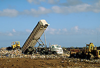 Landfill operation; Self tipping trailer; bulldozer; compactor. Dry sludge stabilized with garbage. Houston Texas.
